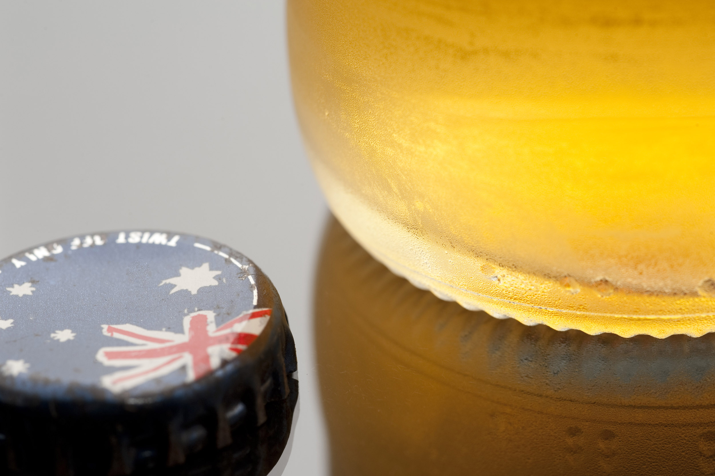a bottle of beer and a bottle cap with the australian flag on it