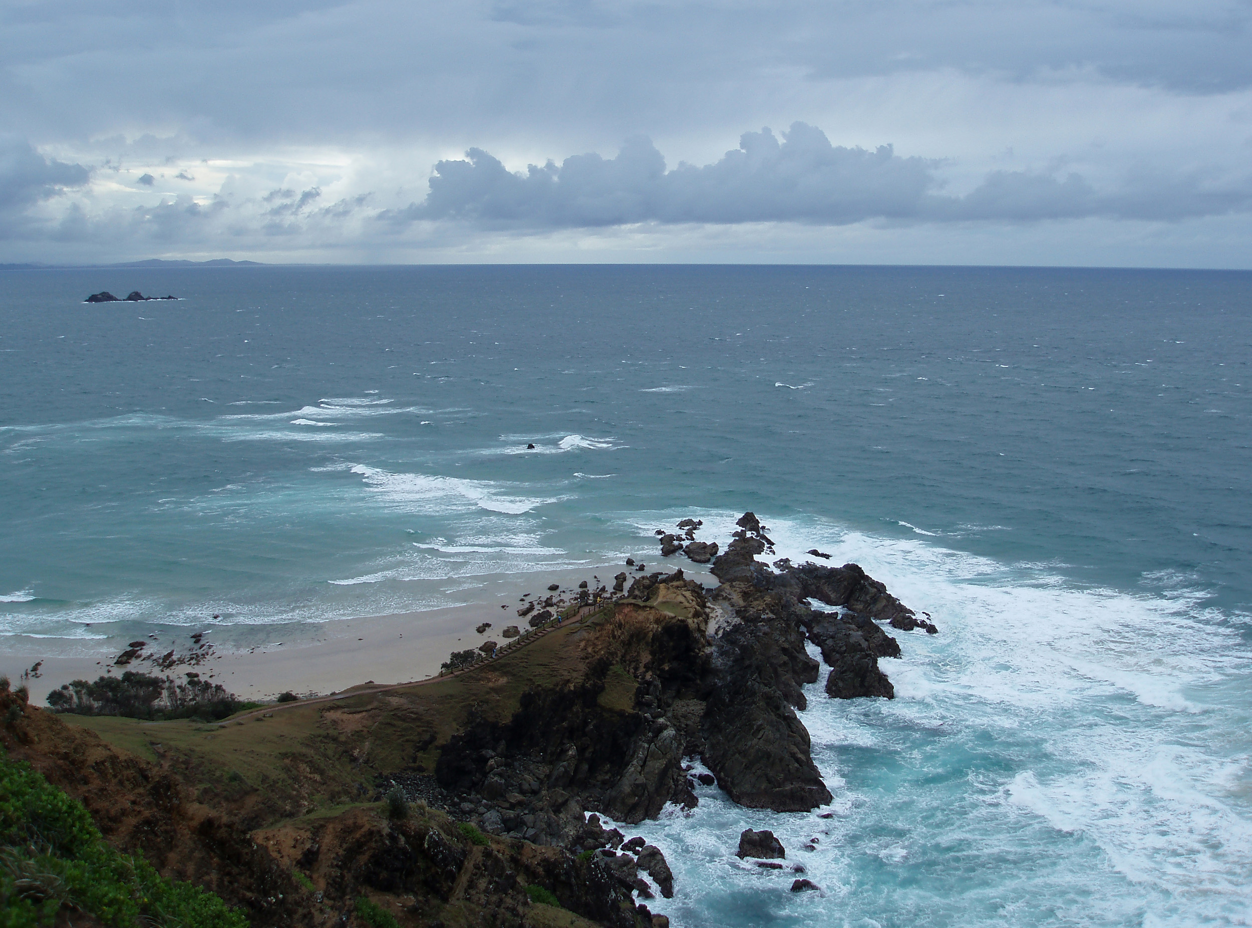 looking down at rocks at the bottom of the cliffs of cape byron, mainland australias eastern most point