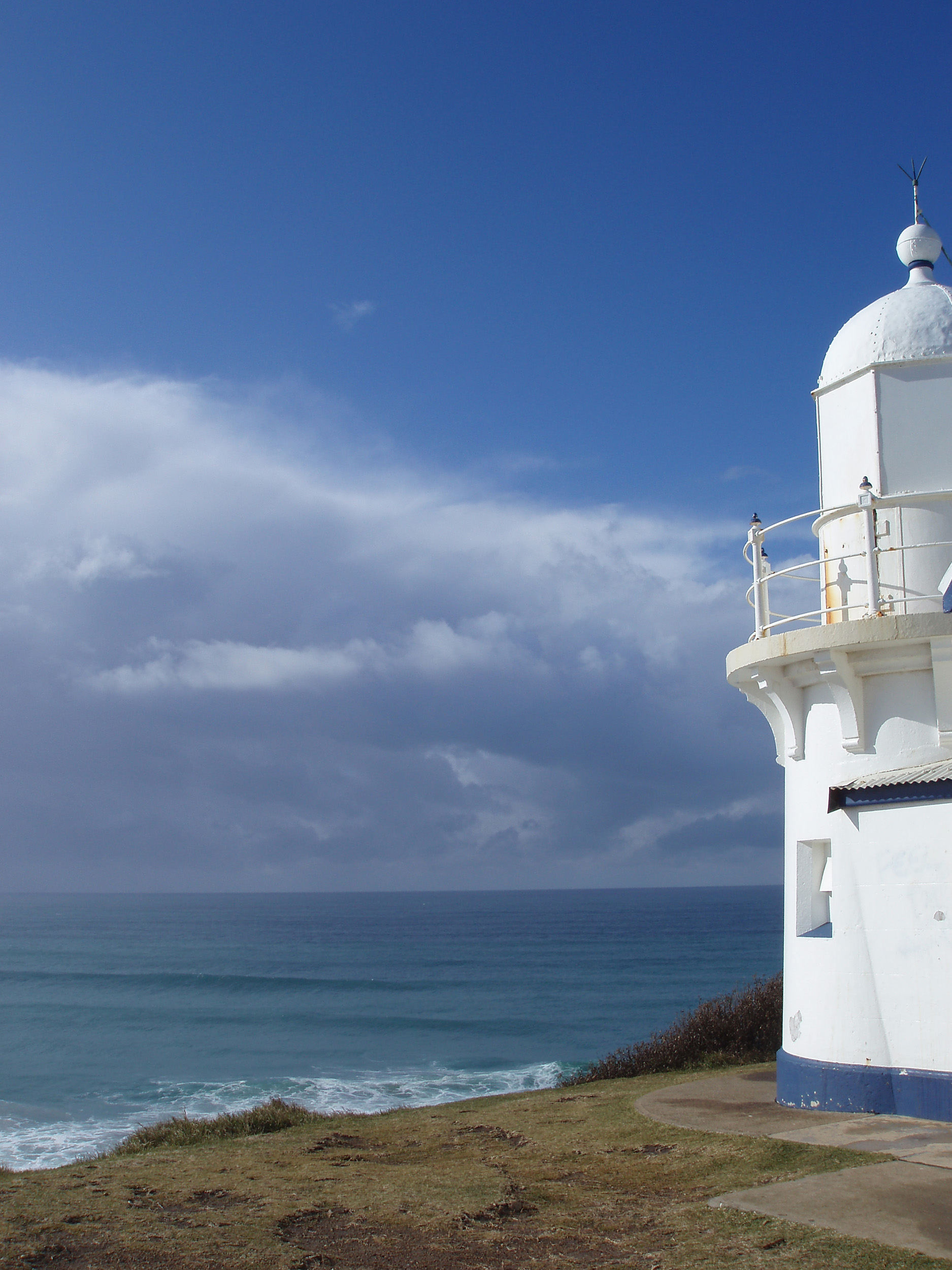 a white and blue painted light house near port macquarie overlooking lighthouse beach