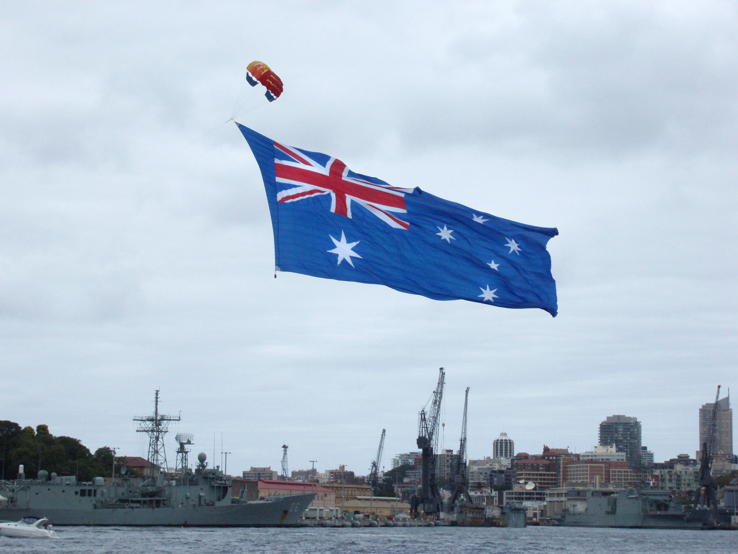 a large australian flag bring flown above garden island dock yard sydney