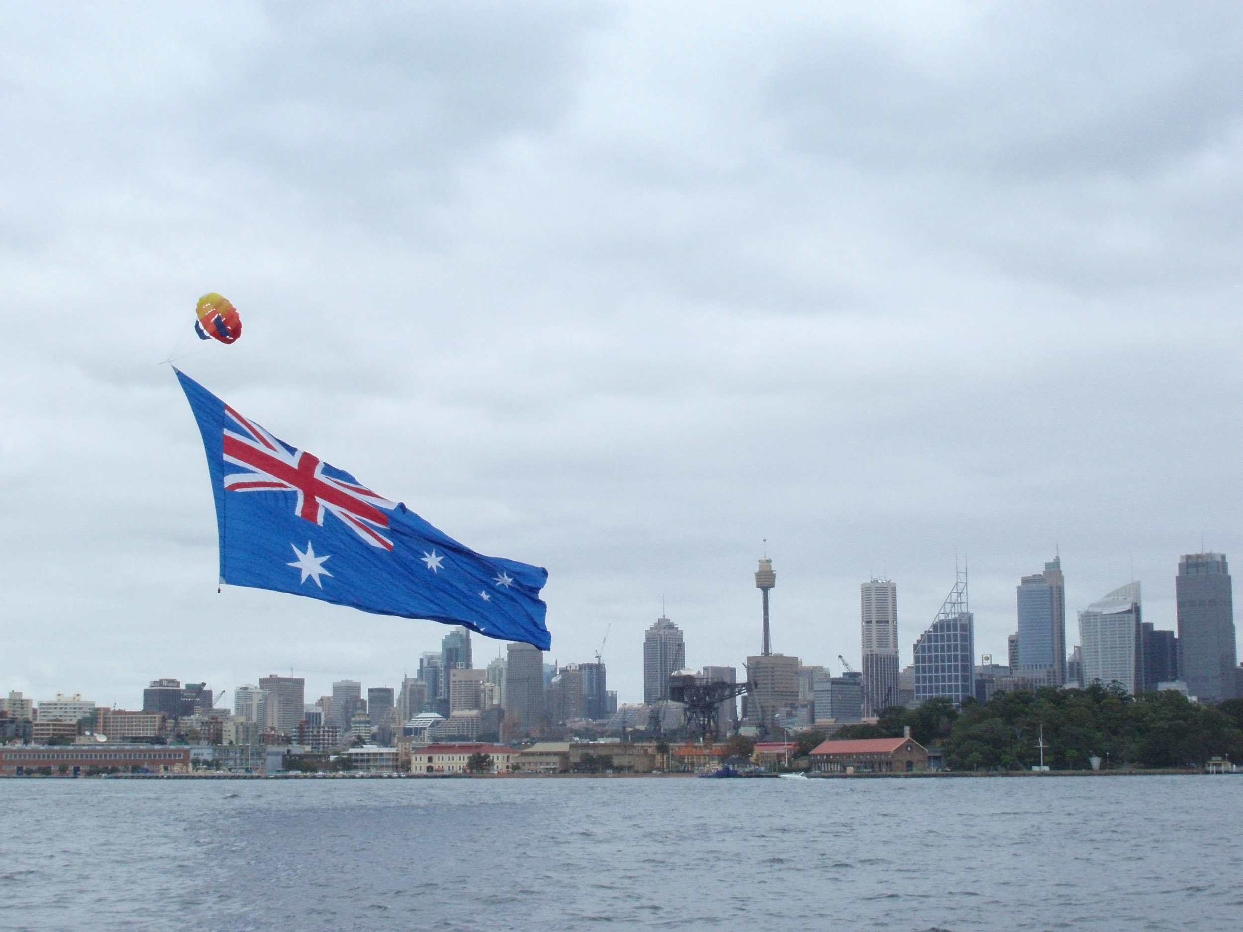 a large flag flying across sydney harbour with the city sykline to the rear