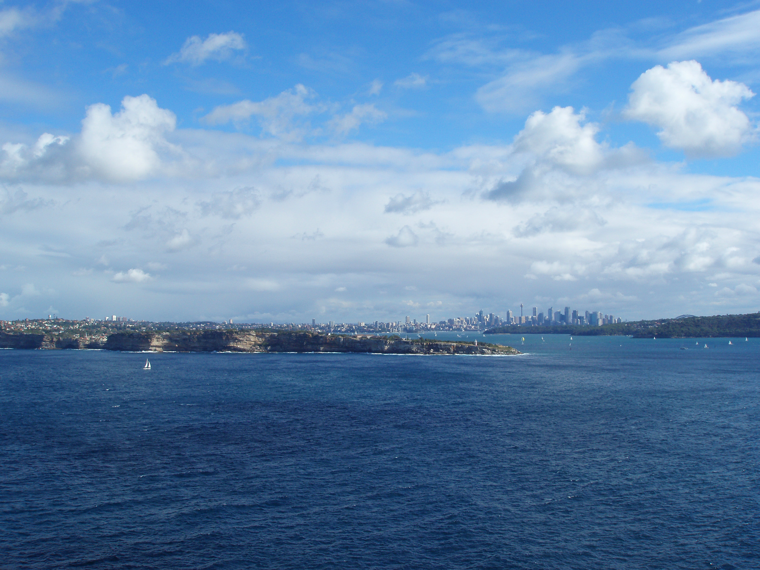 a wide angle image taking in a view of the sydney city skyline, the famous harbour and the hornby nighthouse on south head