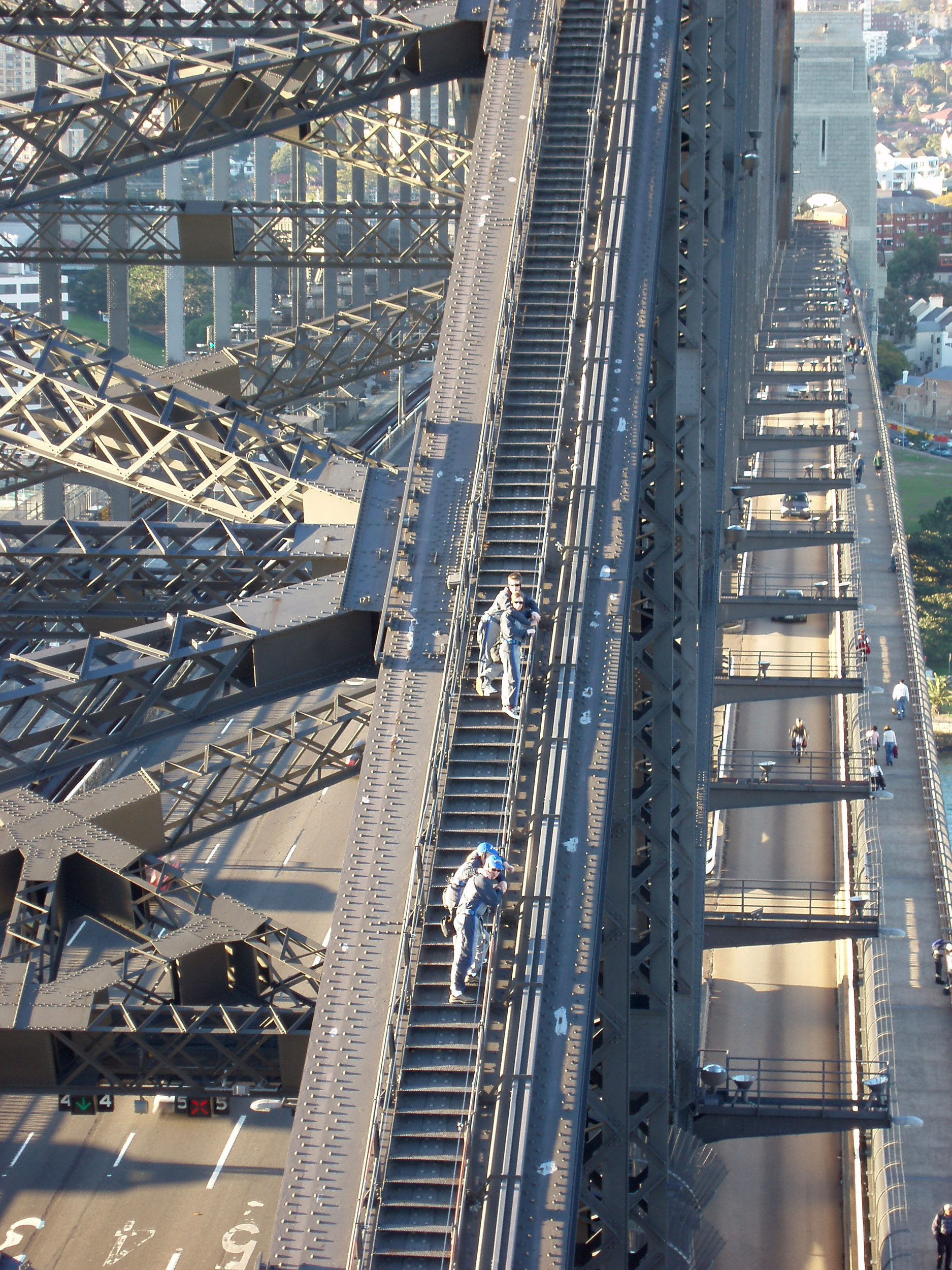 pedestrians and traffic crossing sydney harbour bridge as people climbing the bridge look down from above