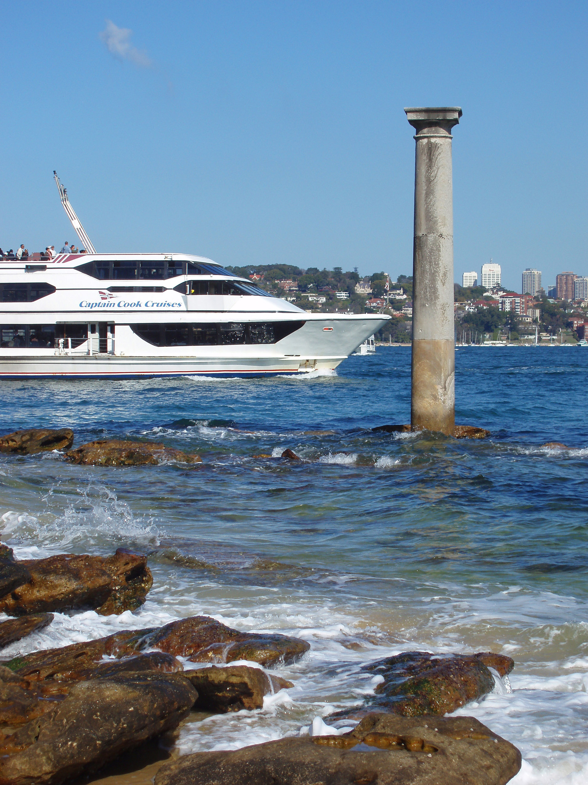 a large harbour cruise boat sailing past the old post office column, sydney harbour