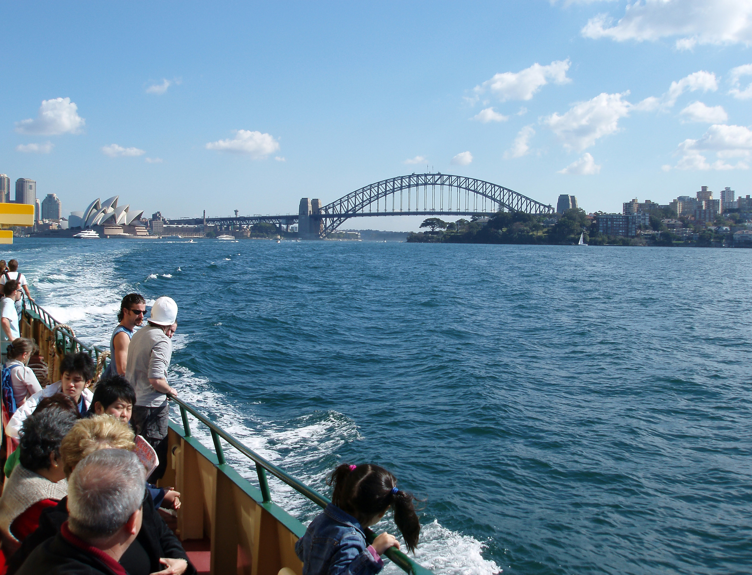 people enjoying the view of sydney harbour bridge from a ferry