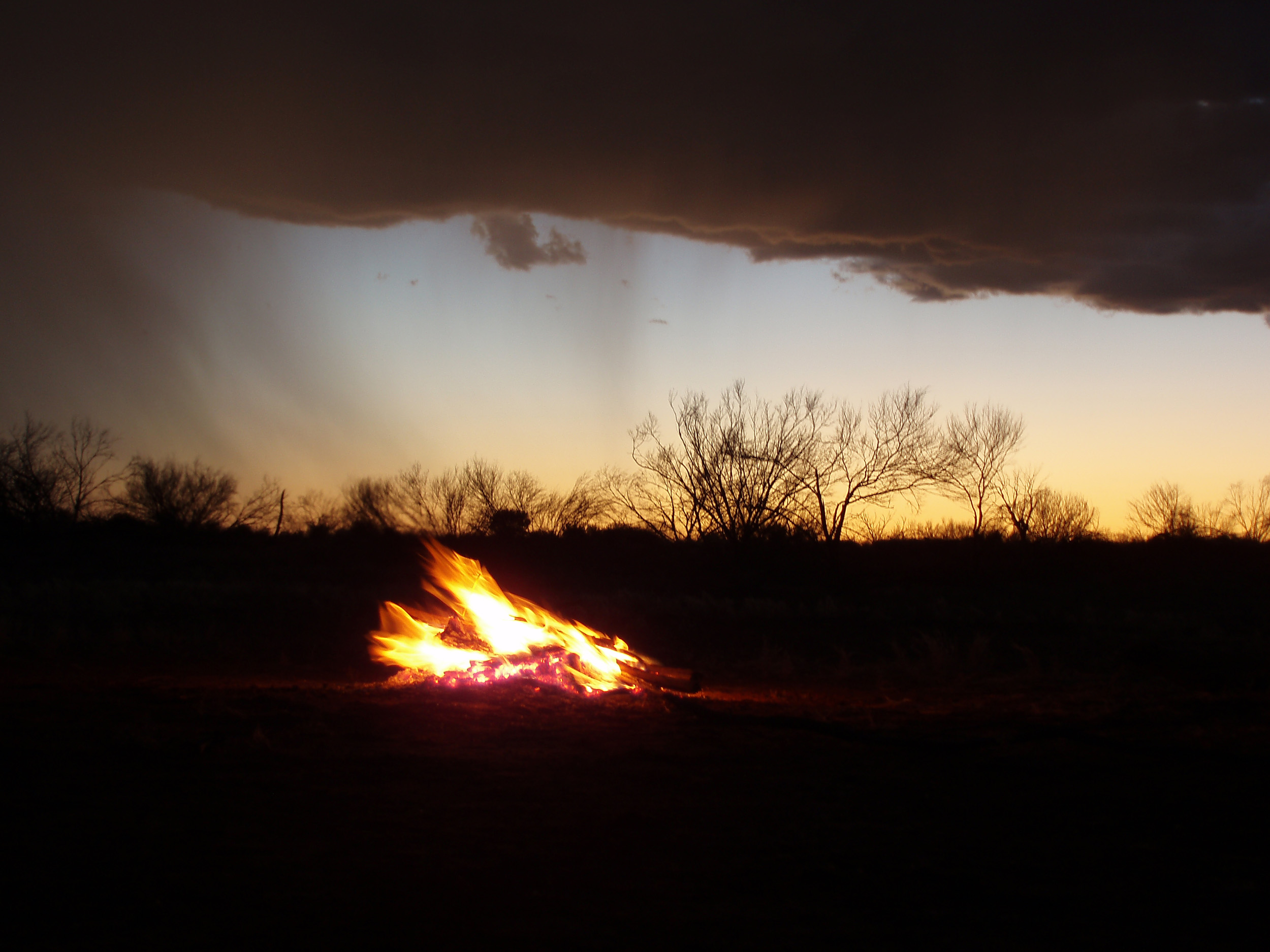 a camp fire at sunset with passing cloud and rain shower