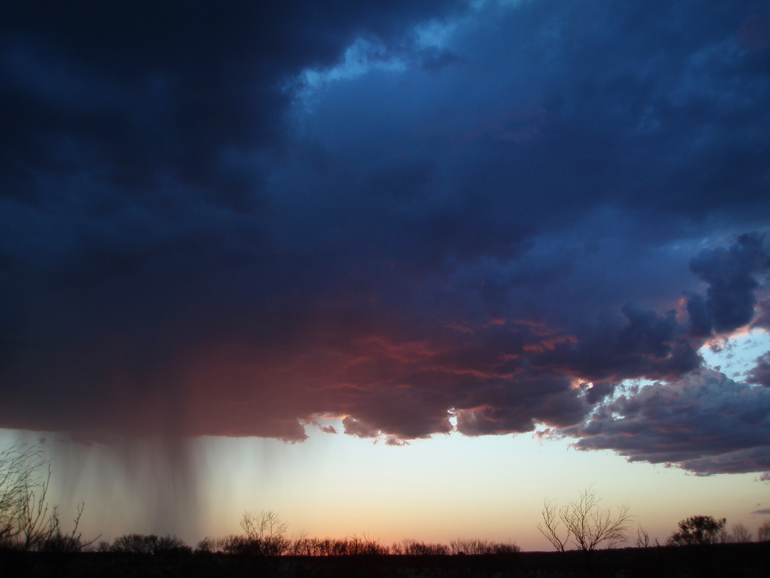 a heavy dark storm cloud dropping rain onto the desert floor at sunset