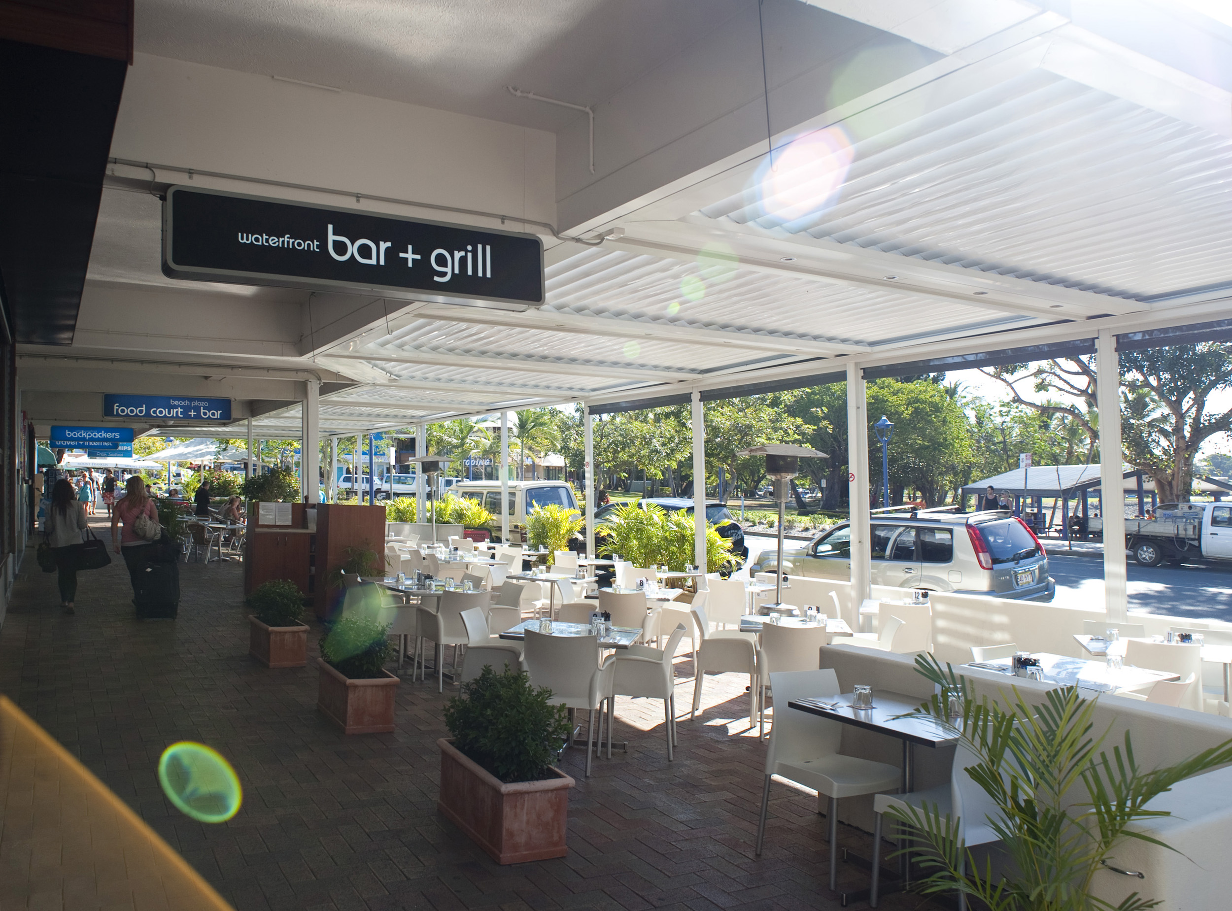 Airlie esplanade dining with an open-air restaurant on a covered porch overlooking a street in Airlie Beach, Queensland, Australia