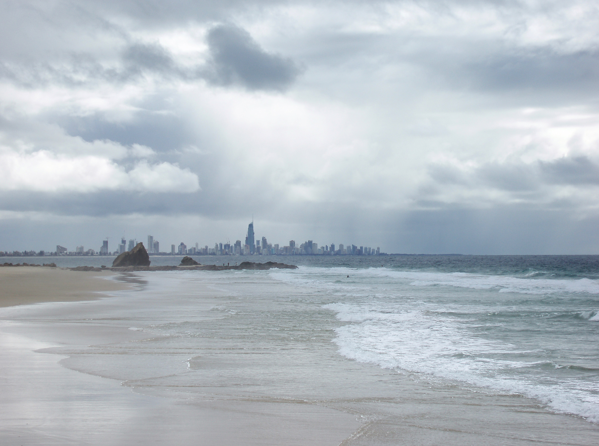 currumbin beach on a cloudy day with the high rise buildings of surfers paradise in the background, gold coast, QLD
