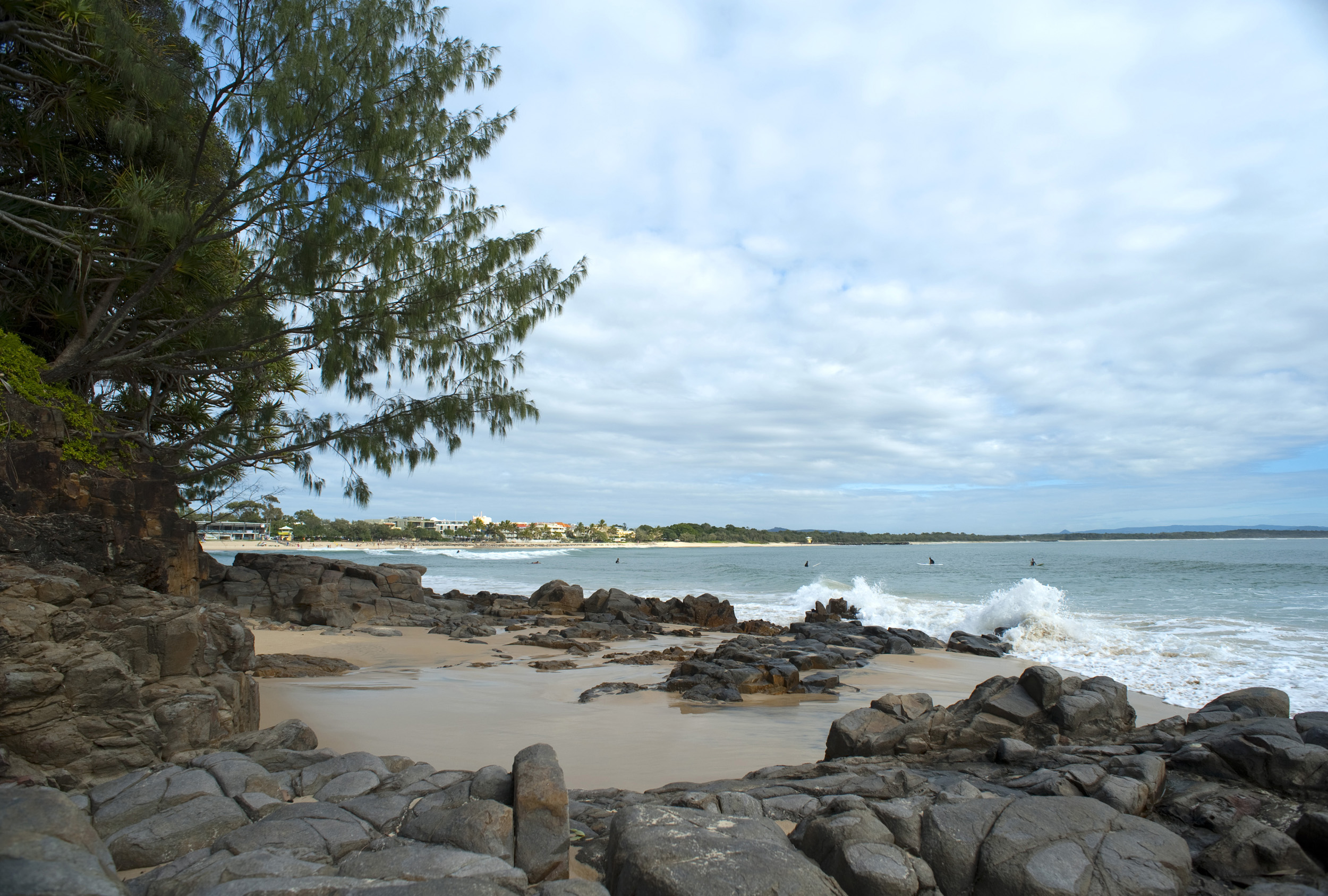 Noosa beach waterfront with a rocky shoreline and breaking waves on a cloudy day