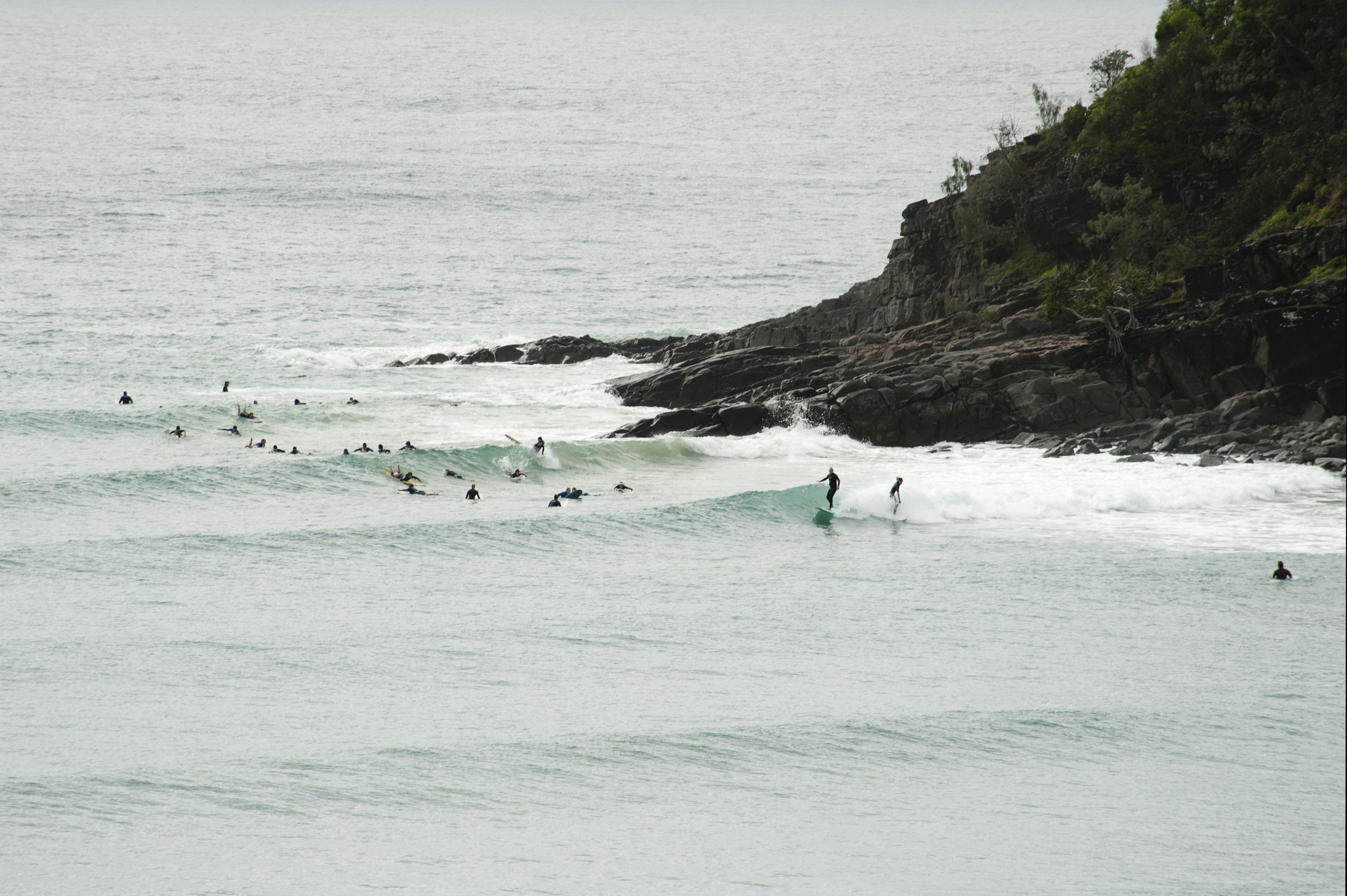 Surfers in the sea at Noosa beach, Australia riding the waves at the bottom of a rocky headland as they wait for a roller to catch a ride