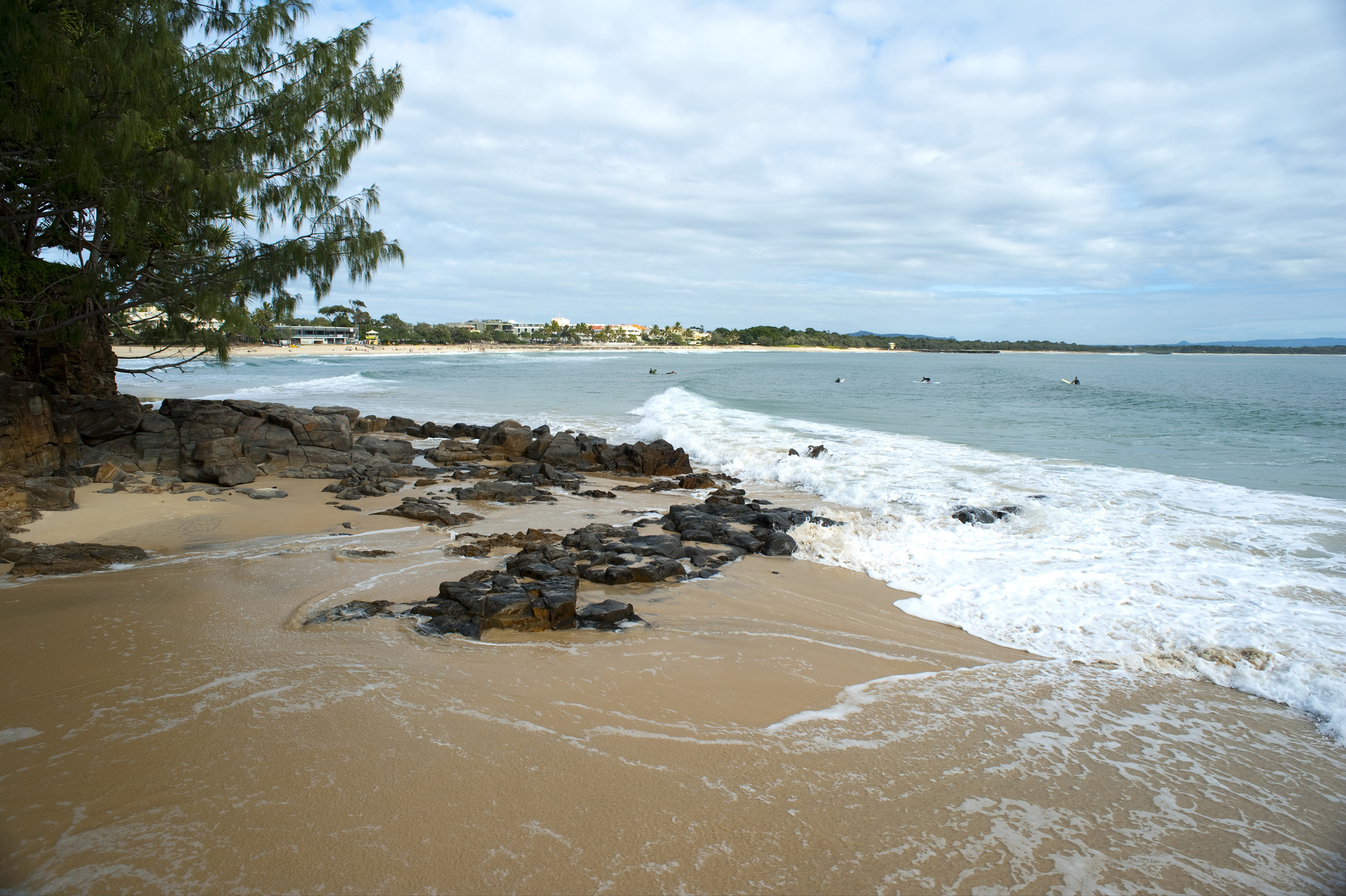 Rocky shoreline with golden sand at Noosa beach in Queensland, Australia, a popular tourist resort and destination for surfers