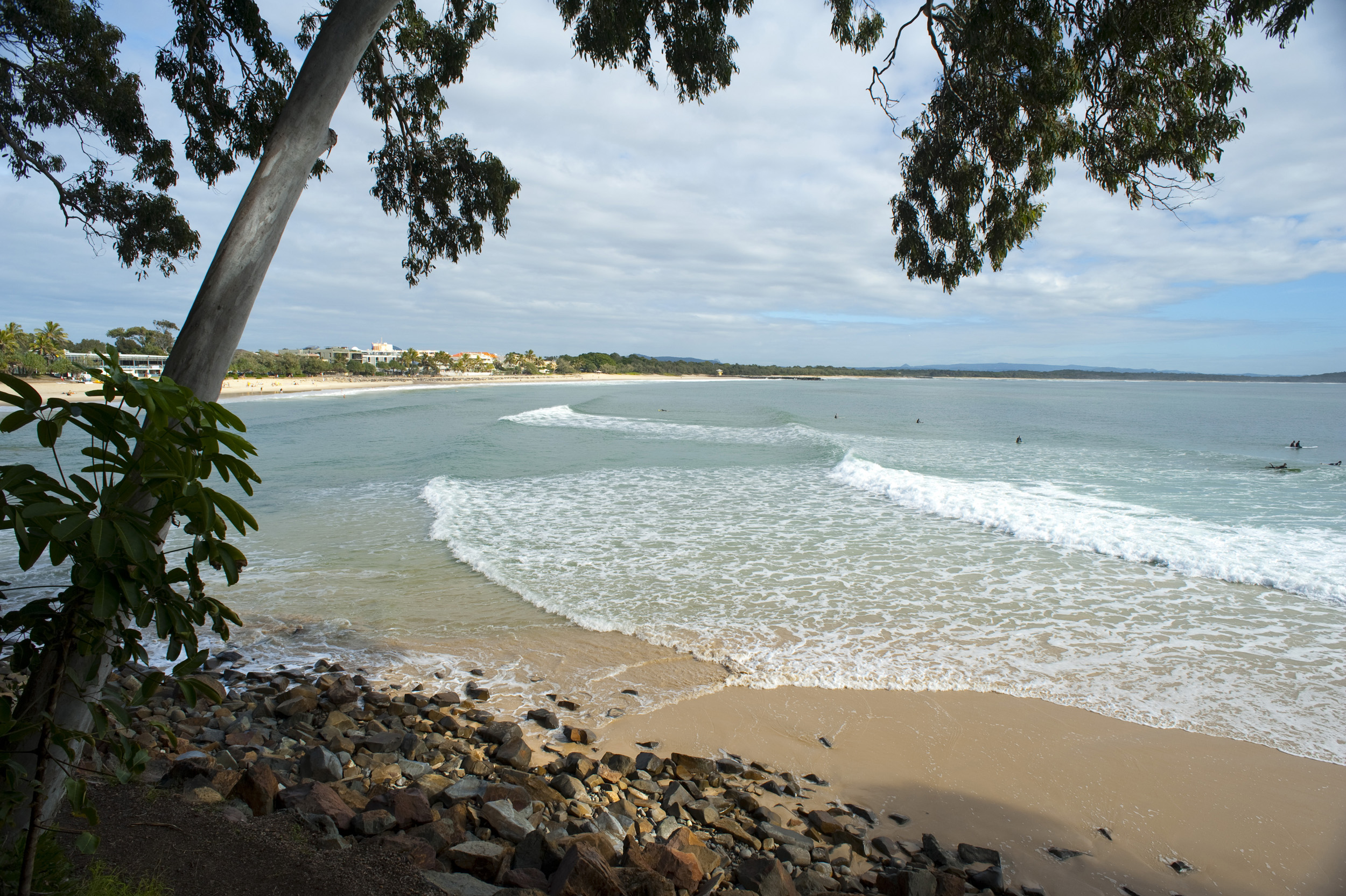 Tranquil tropical beach at Noosa, Queensland with gentle surf lapping the golden sand in this popular resort