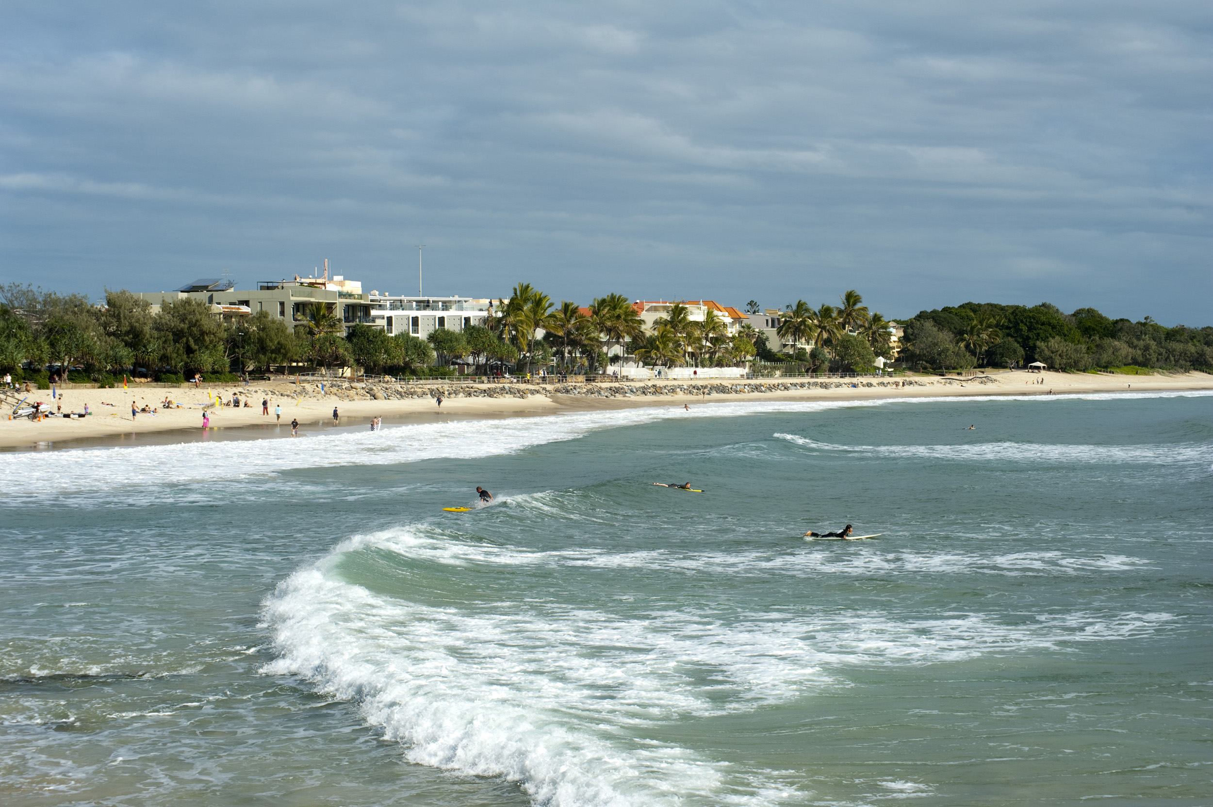 Surfers and holidaymakers enjoying the surf on Noosa Beach in Queensland, Australia