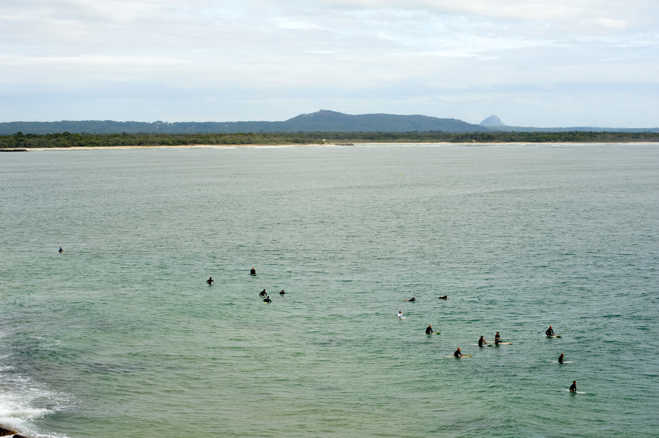Group of surfers waiting on their boards at sea for a suitable wave off the beach at Noosa Beach in Queensland, Australia