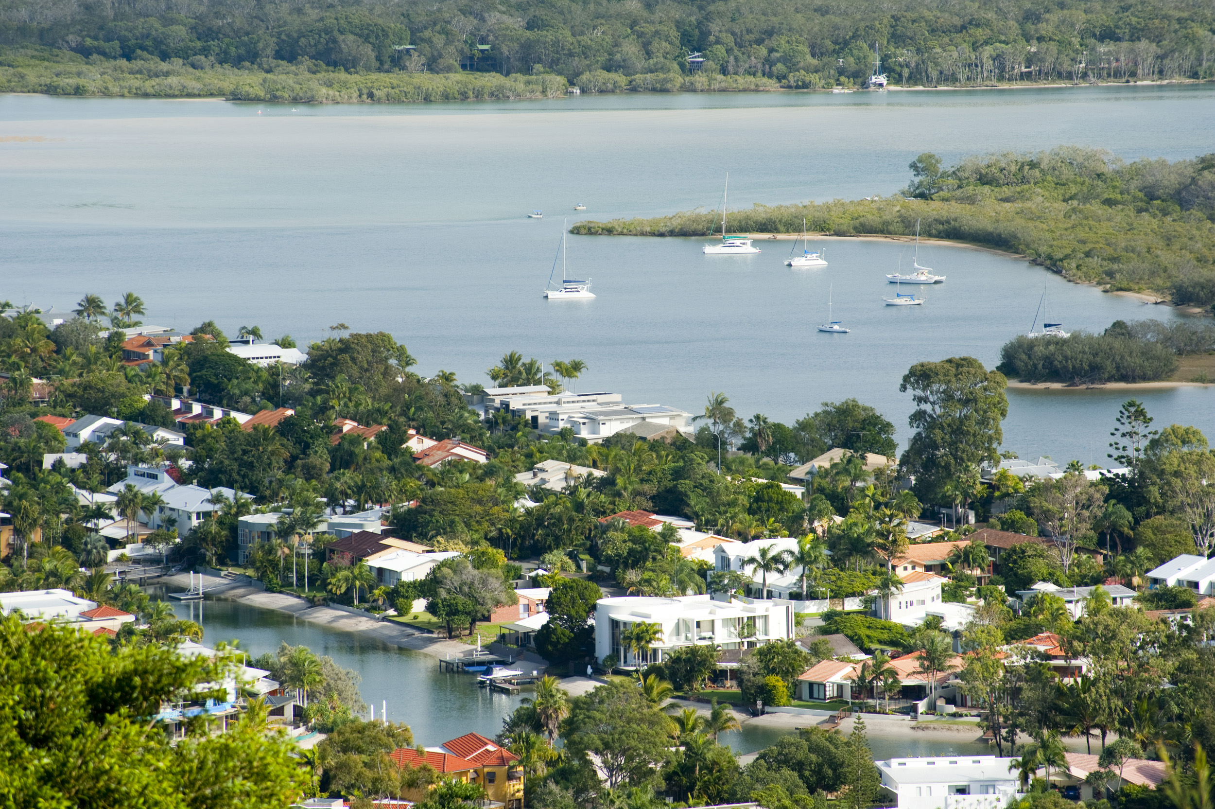 Luxury houses on the waterfront at Noosa, Queensland, Australia nestling in lush trees on the banks of the Noosa River