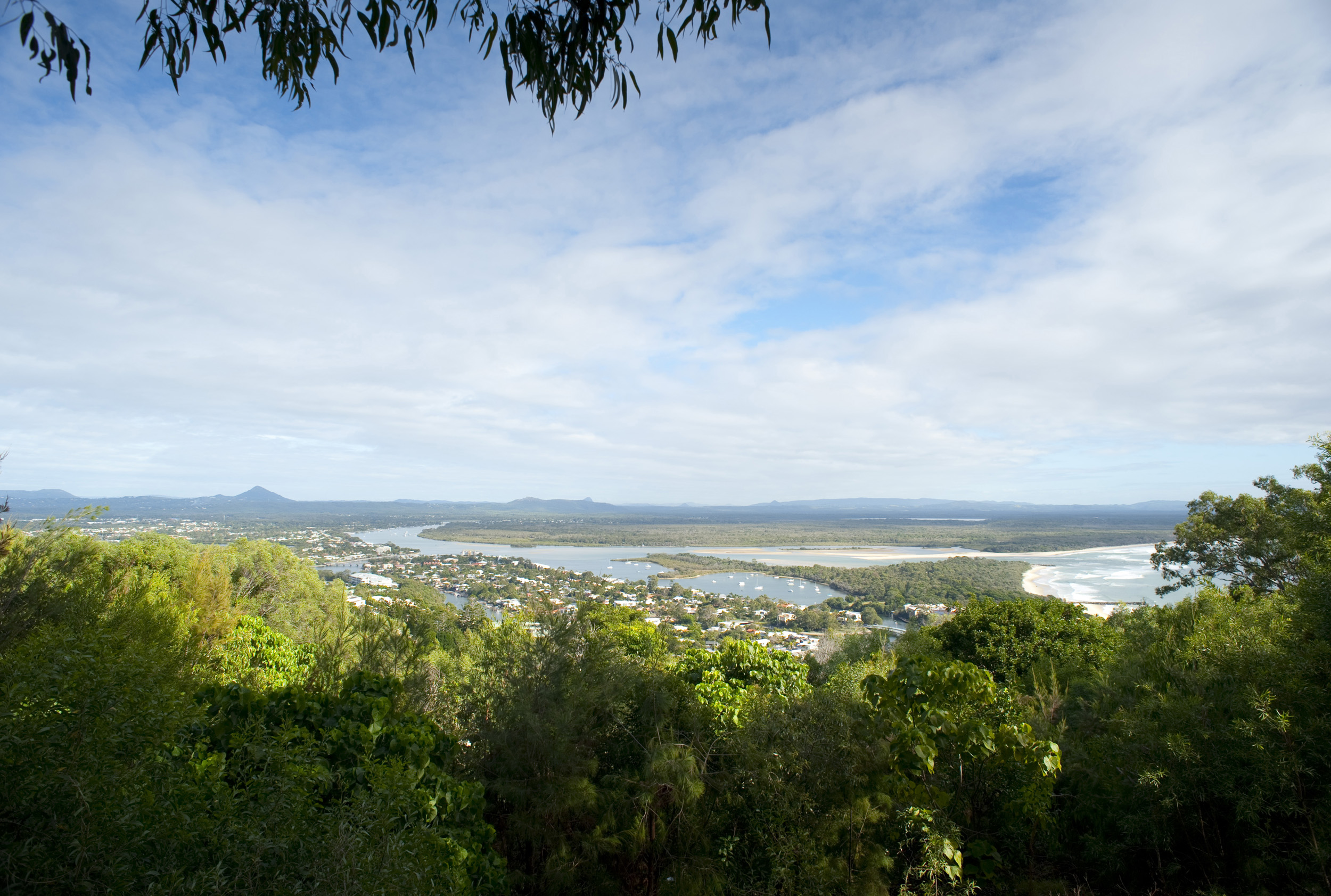 Noosa panorama showing the estuary of the Noosa River amongst lush tropical vegetation and a portion of the coastline as it enters the ocean