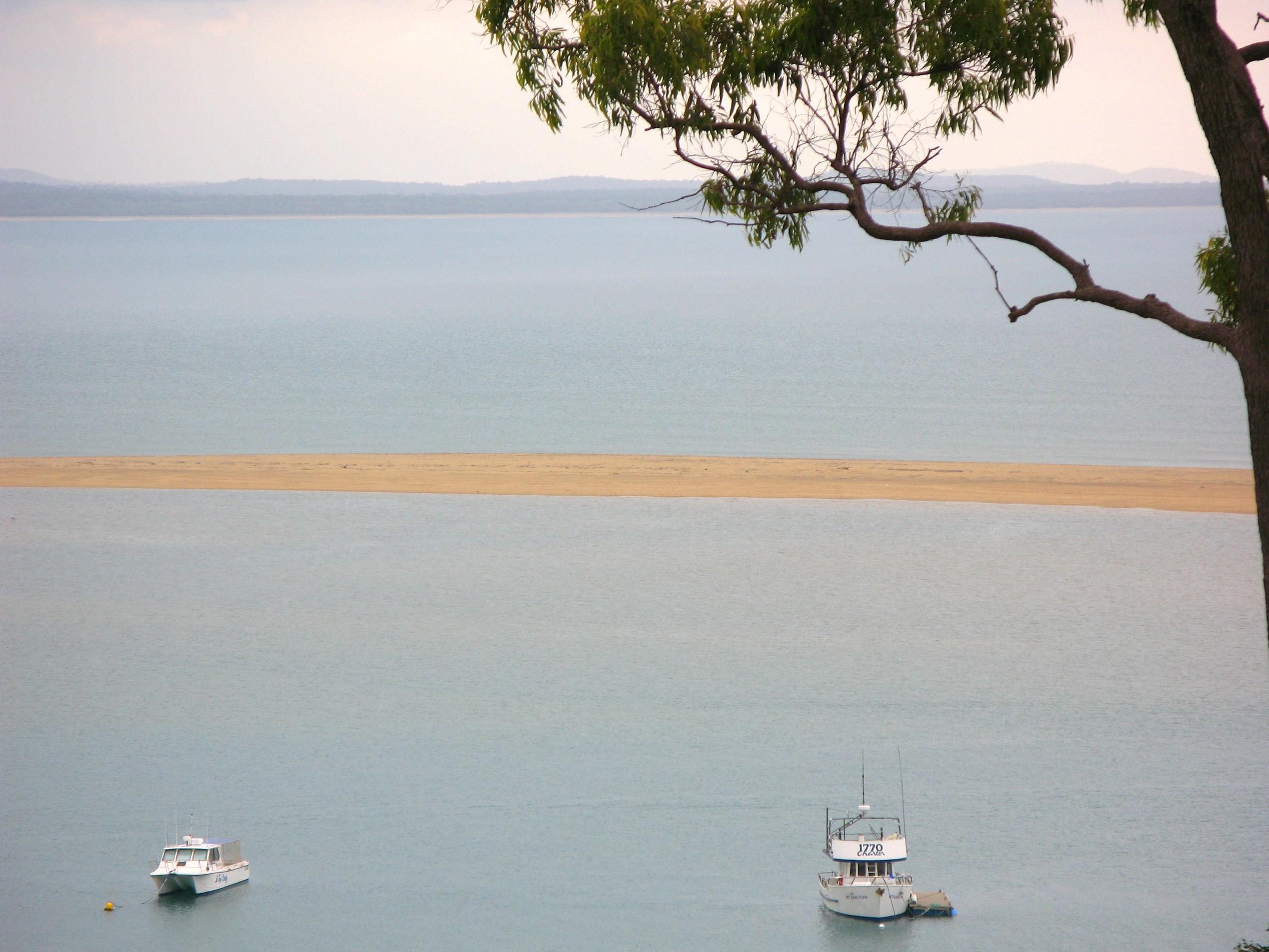 boats moored behind the sandbar at town of 1770, queensland