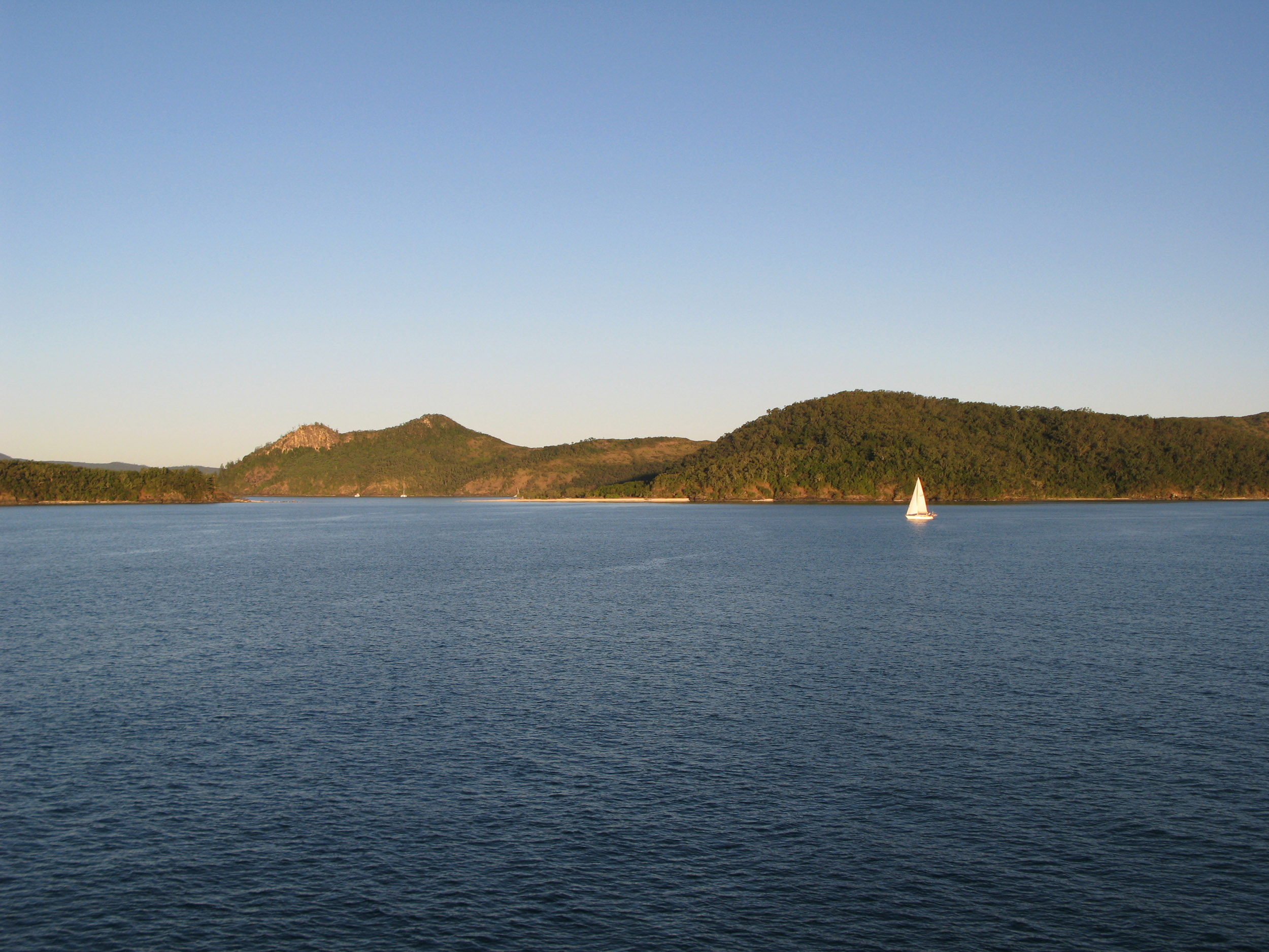 a lone sailing boat exploring the whitsunday islands