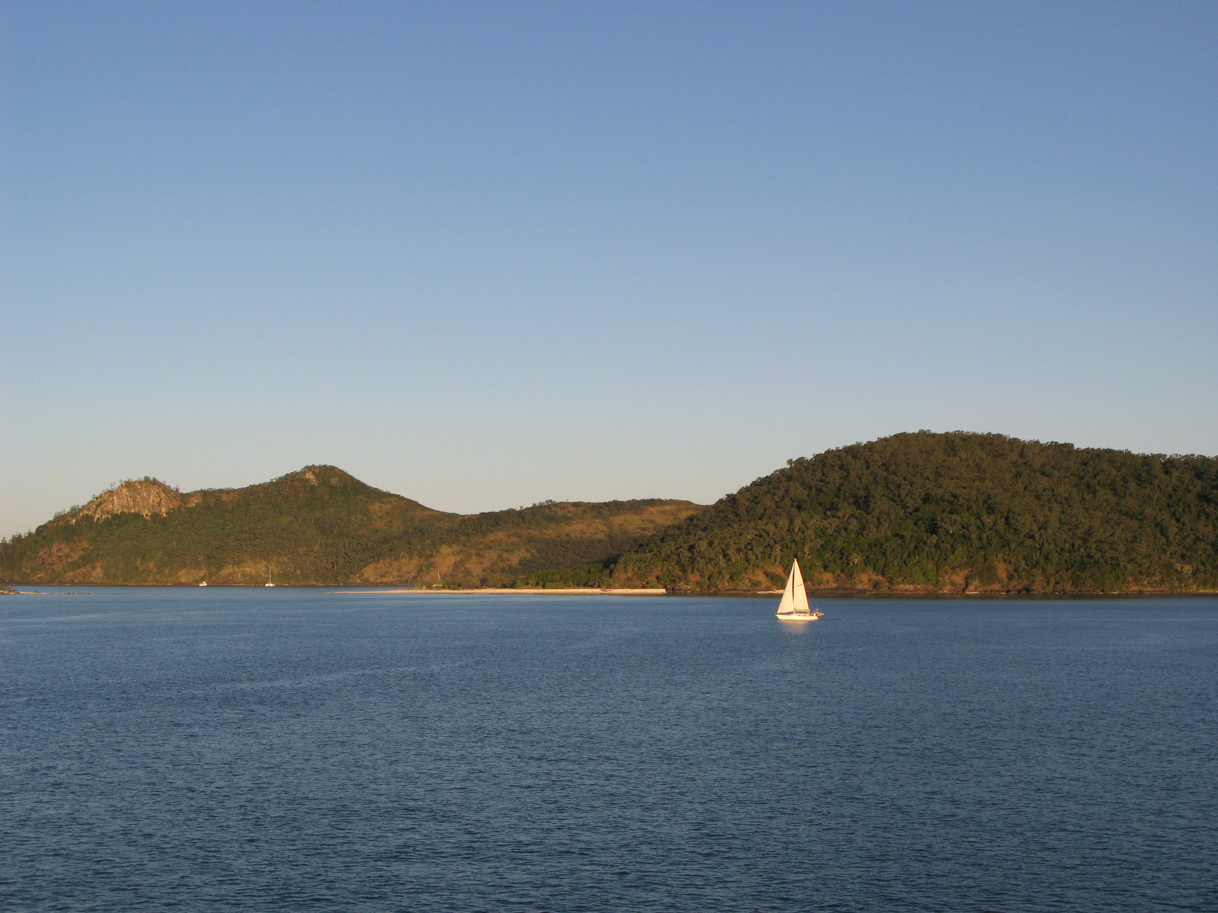 a single sailing boat navigating its way around the whitsunday isalnds, queensland