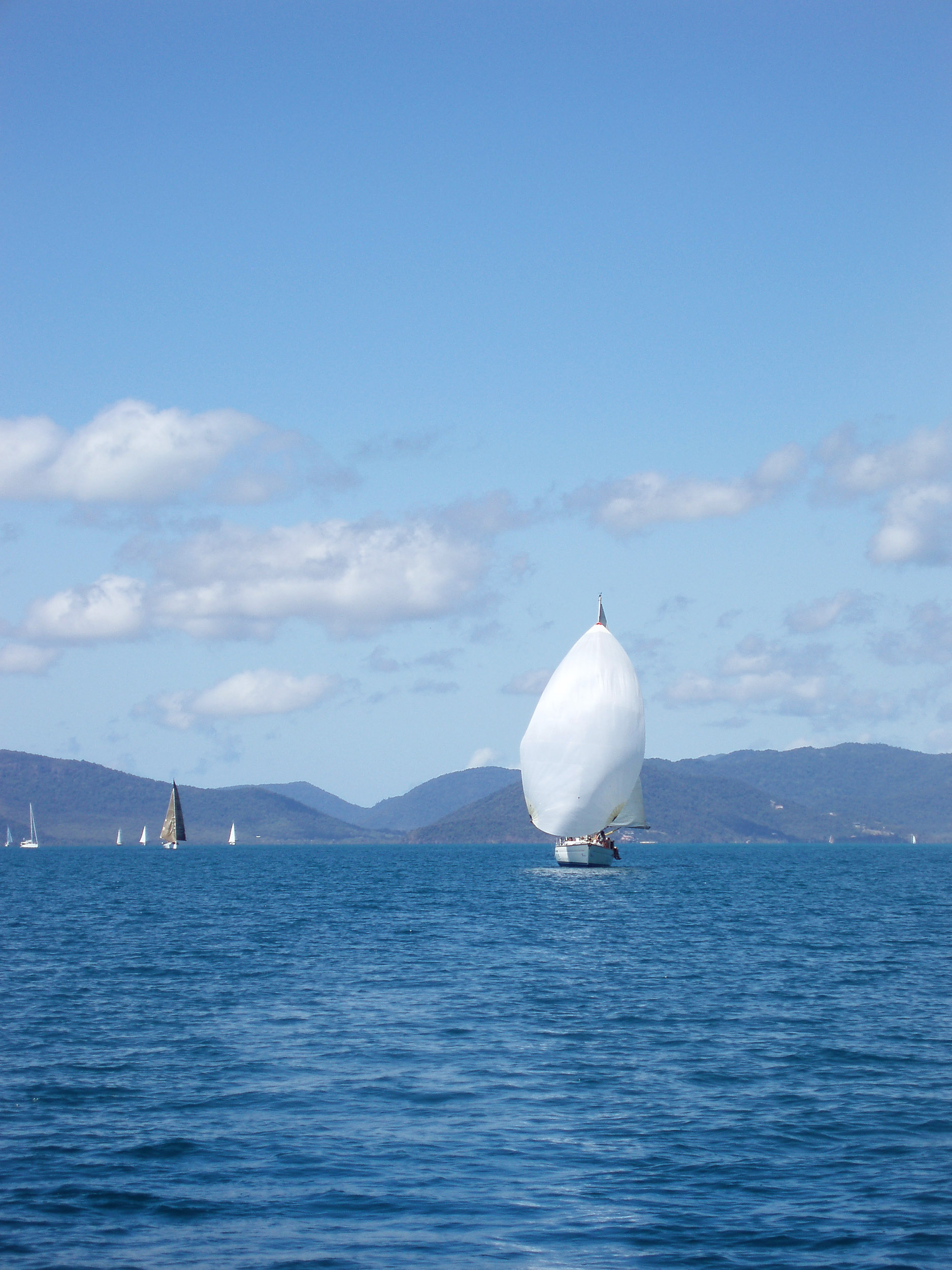 a yacht sailing with a large white spinnaker sail over a calm ocean