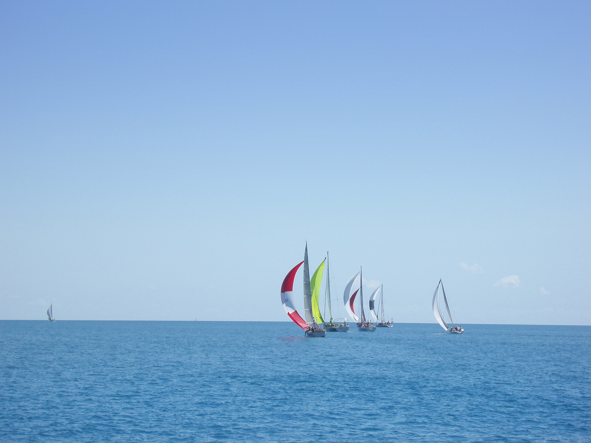 a yacht race in light air, several boats on a calm ocean flying spinnaker sails