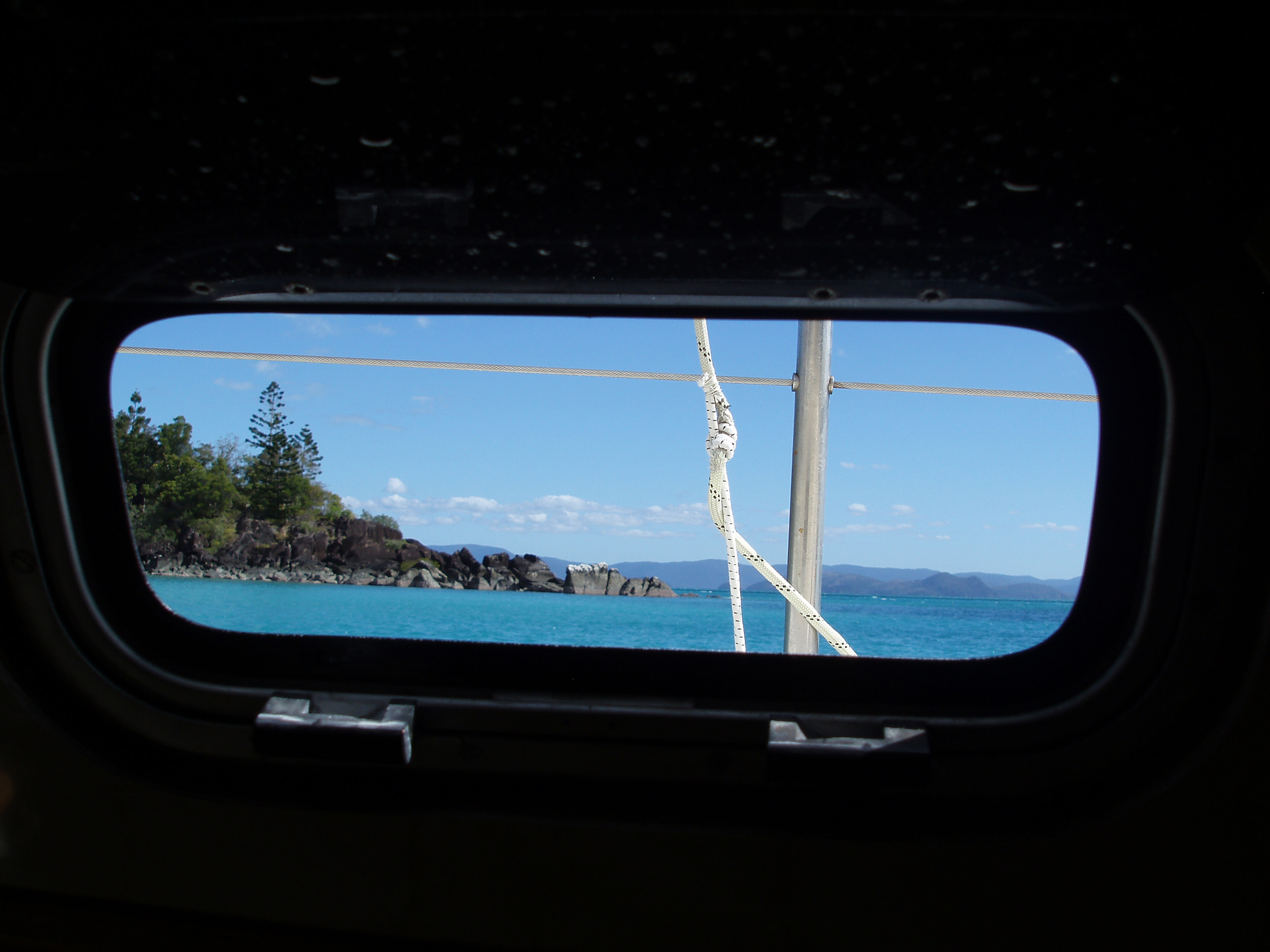 the view from a porthole on a cruising sailing yacht in the whitsundays