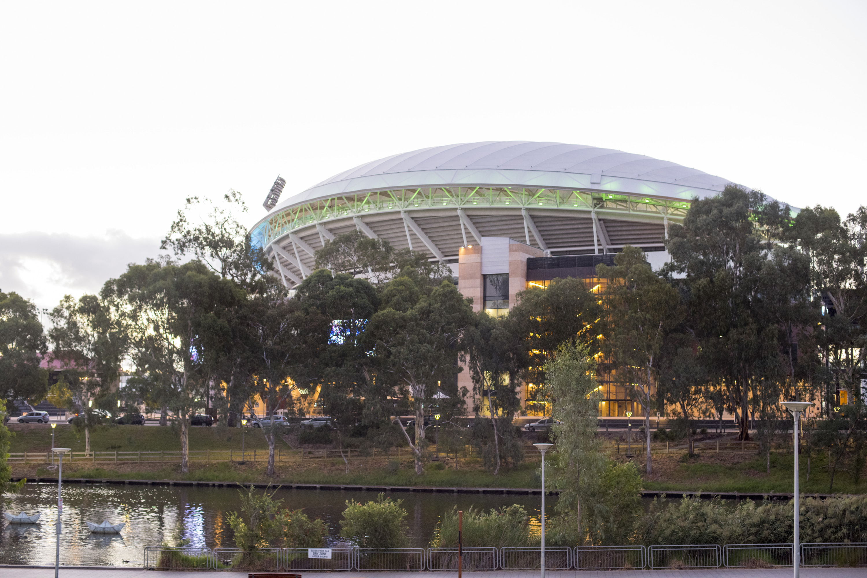 View of the Adelaide Oval Cricket Ground over leafy green shrubs in the Adelaide, Australia parklands providing an international sports venue