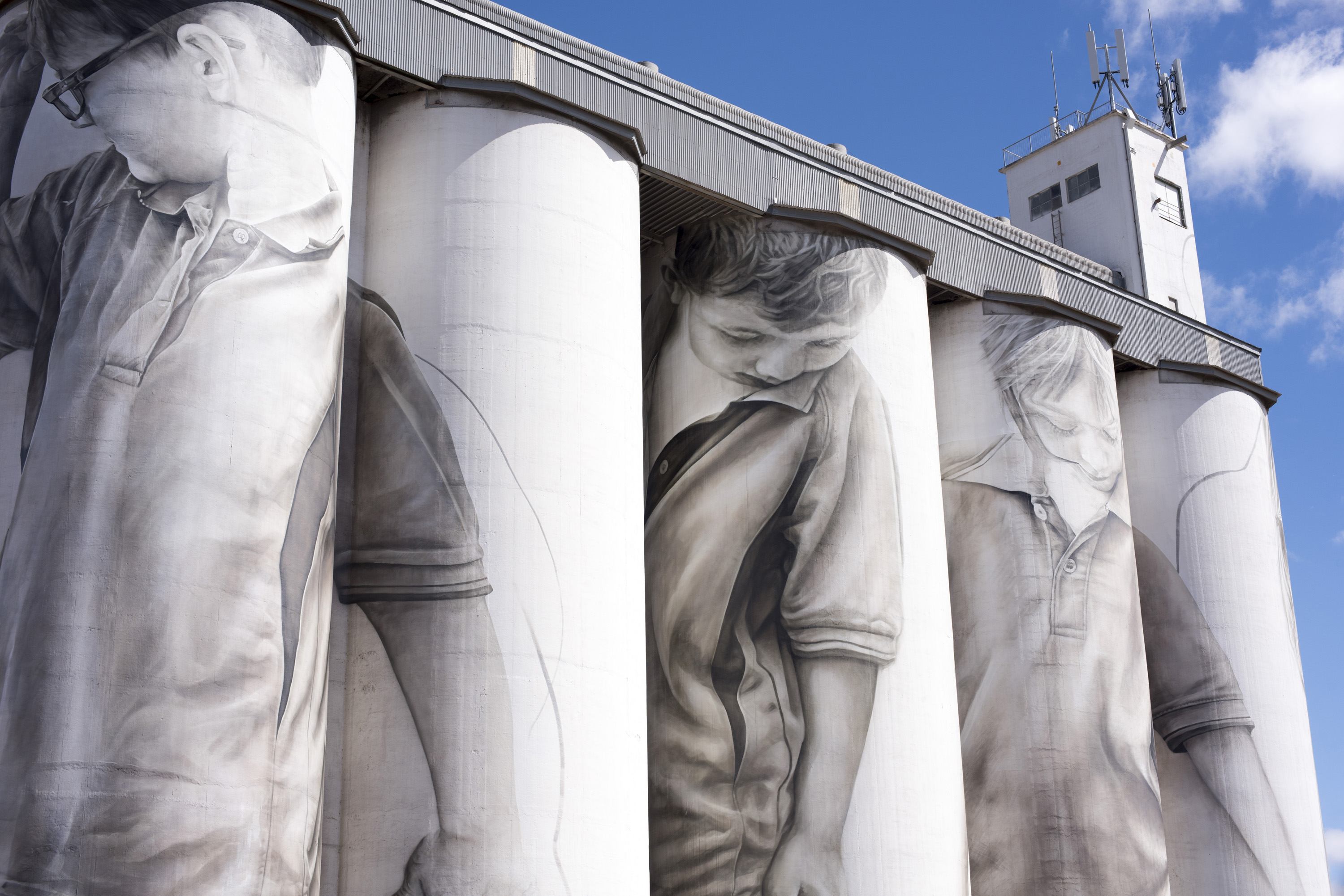 Closeup of large decorated grain silos in Coonalpyn, South Australia with murals of men drawn on the facades against a blue sky