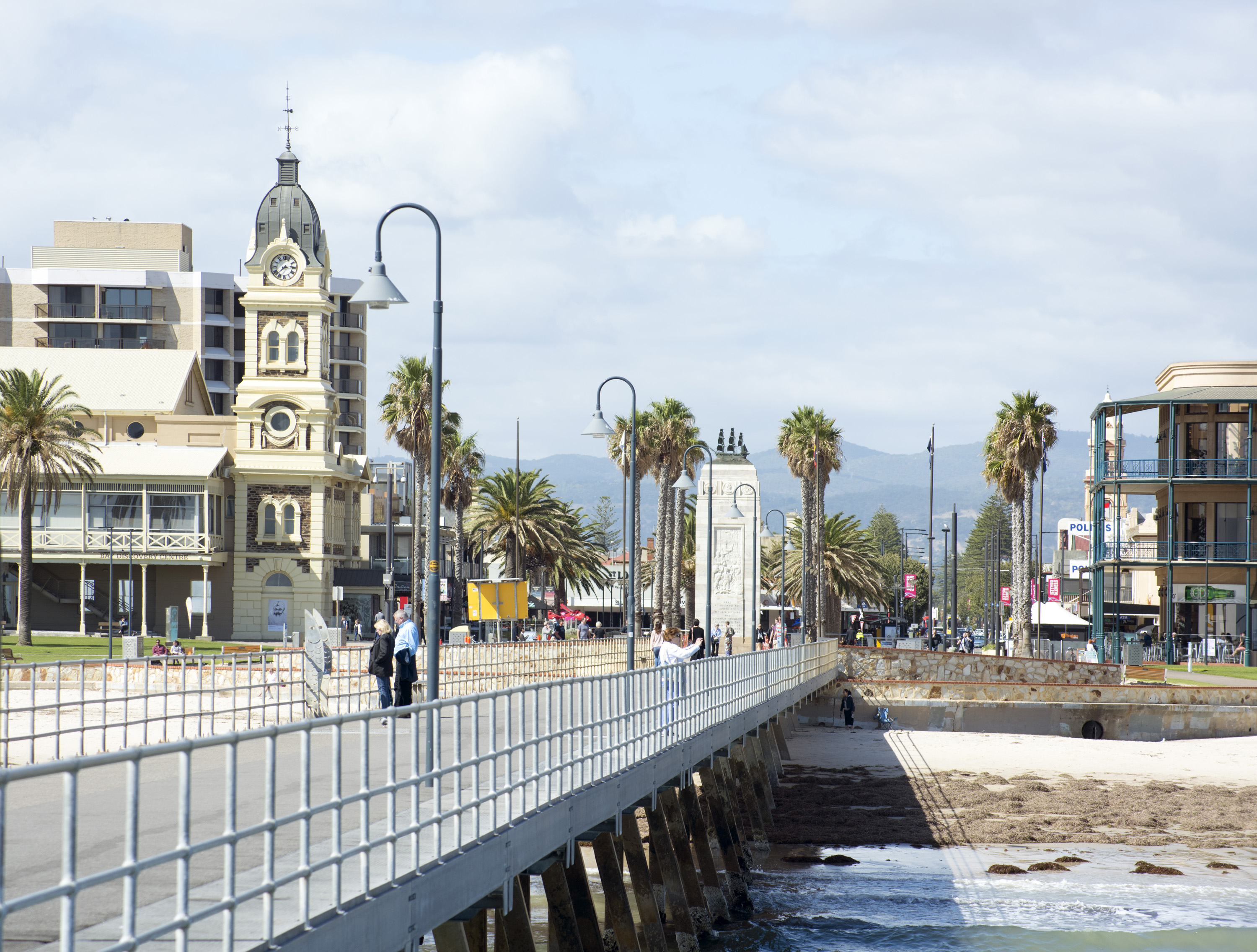 View from the pier at Glenelg, Adelaide, Australia looking back at historic heritage buildings with people standing on the promenade admiring the ocean