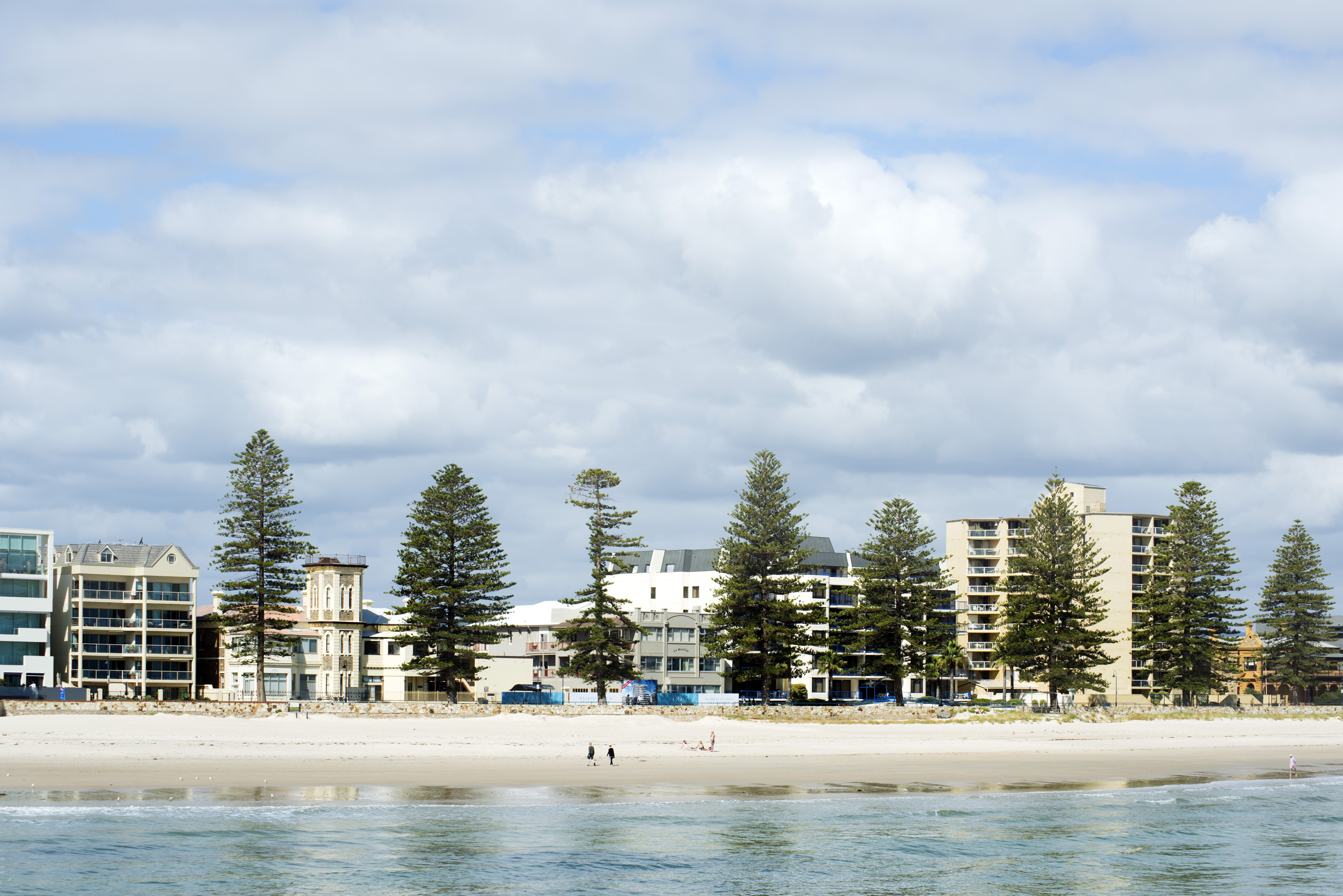Waterfront apartments in Glenelg, Australia overlooking a sandy tropical beach with coniferous trees viewed across the sea on a cloudy day