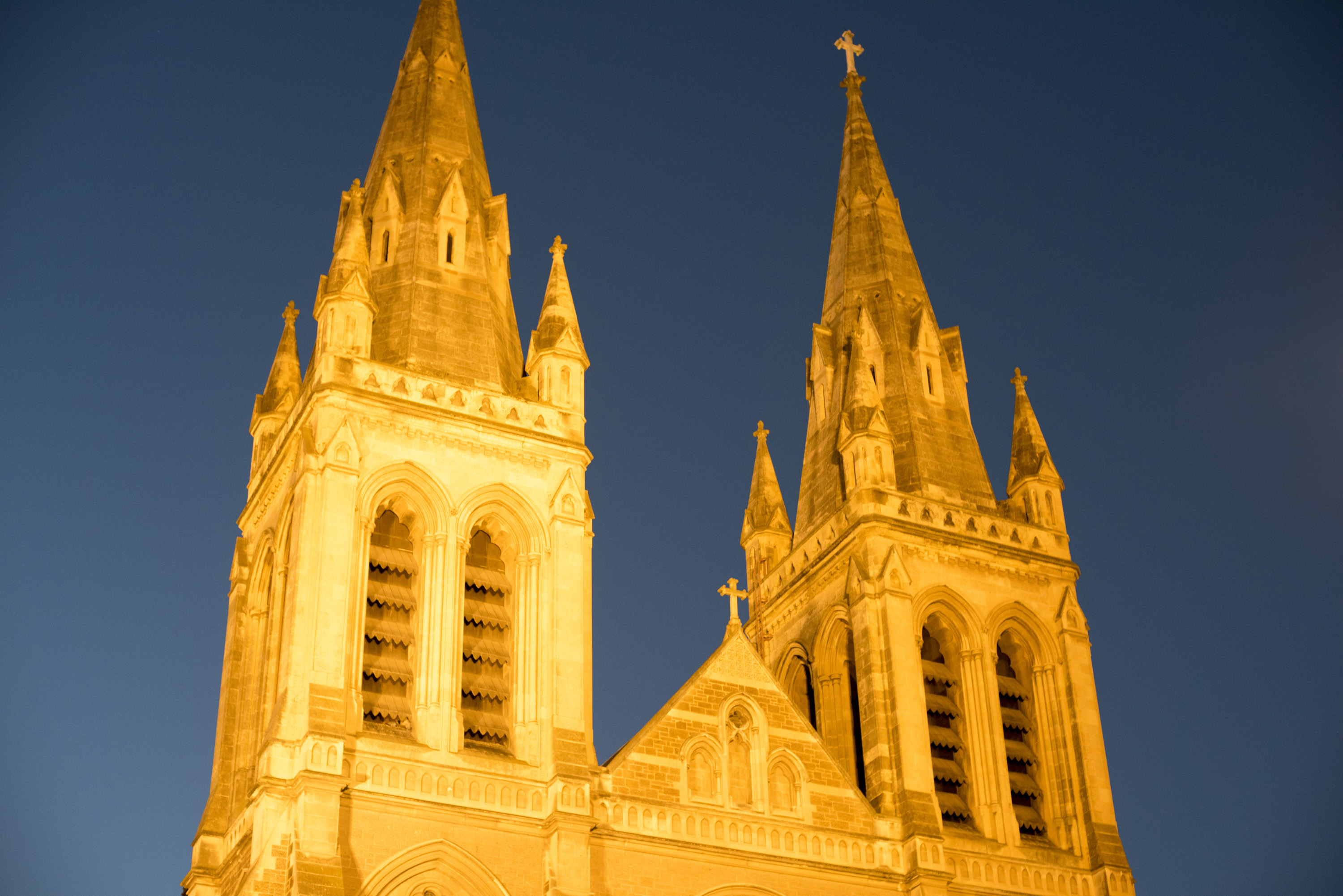 Illuminated twin spires of St Peters Cathedral in Adelaide, Australia at twilight in a close up low angle exterior view