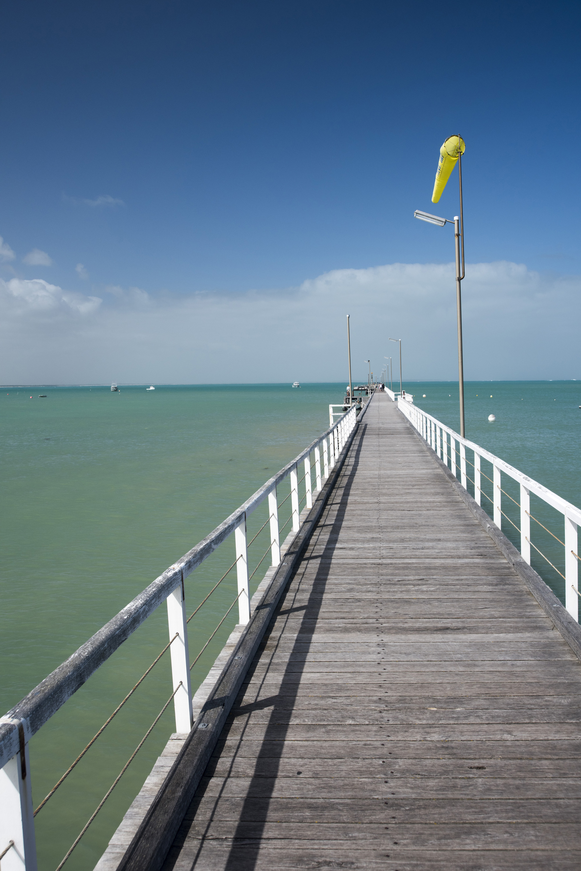 The long beachfront jetty or boardwalk at Beachport, Australia extending away into the ocean with a yellow wind sock against a blue sky