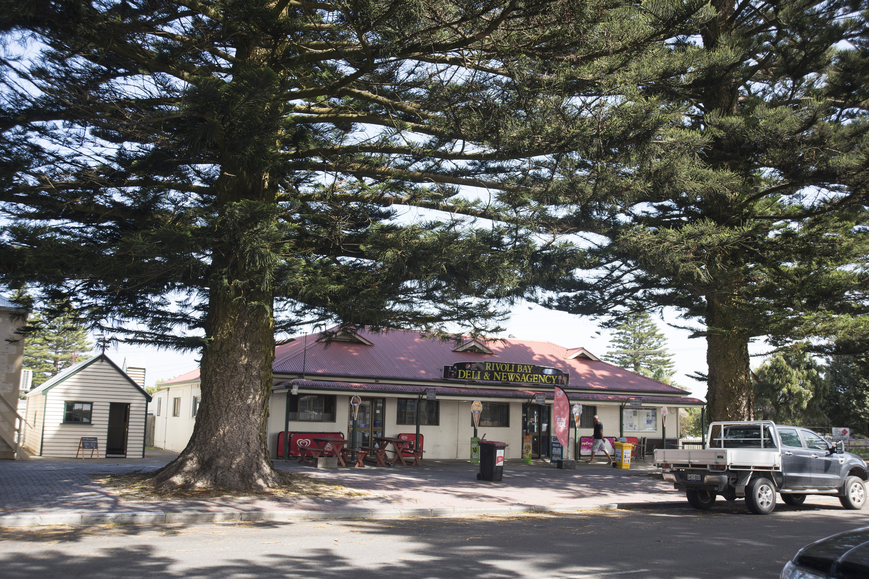 Historic heritage buildings in Beachport, South Australia in a street scene with quaint old store between two large pine trees
