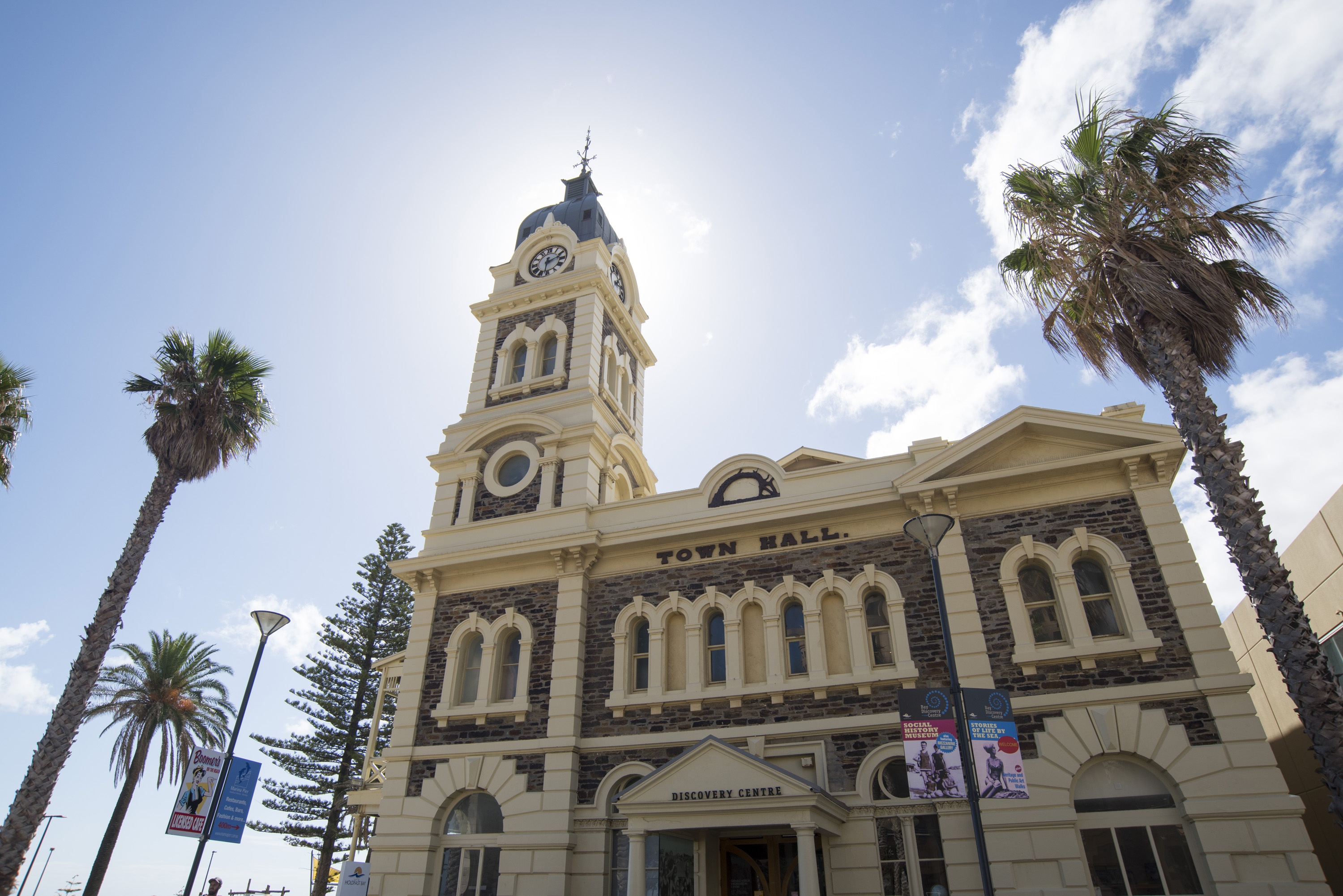 The front facade of the Town Hall, Glenelg, Adelaide, South Australia with its arched windows and clock tower flanked by tall tropical palm trees